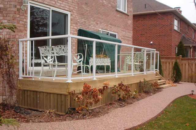 White-Large-Glass-Panel-Railing-on-wodden-deck-with-brick-house